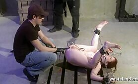 Naked slave chained to a pallet and made to cumming by two Masters